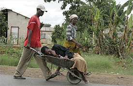 A woman suffering from the symptoms of cholera is taken in a wheelbarrow to a clinic in Harare December 12, 2008.REUTERS/Philimon Bulawayo.