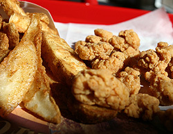 An order of french fries and chicken sit on a tray at a KFC fast food restaurant in New York October 30, 2006. KFC, a unit of Yum Brands Inc, on Monday said it will switch to a cooking oil with no trans fat in all its U.S. fried-chicken restaurants by April 2007. Yum Brands joins hamburger chain Wendy's International Inc as many local governments, including new York City, look at banning the artery-clogging trans fats. Fast-food restaurants have come under increasing criticism that their food contributes to obesity. REUTERS/Shannon Stapleton.
