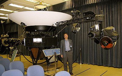 Krimigis standing by the Voyager proof-test model spacecraft on display at the Jet Propulsion Laboratory. The LECP (Low Energy Charged Particle) instrument for which he is Principal Investigator can be seen above his left shoulder.
