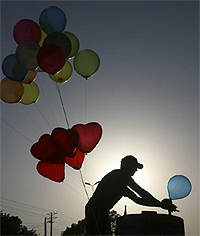 A man is silhouetted as he inflates balloons to sell in Lahore May 9, 2010. REUTERS/Mohsin Raza.
